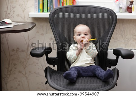 The baby boy sitting on a office chair at home - stock photo