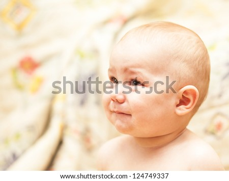 The baby cries and calls mum sitting at floor - stock photo