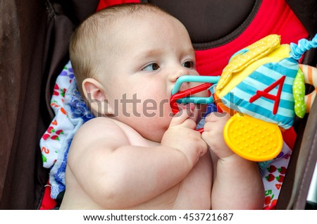 The baby playing with rattle sitting in a wheelchair. the child is teething - stock photo