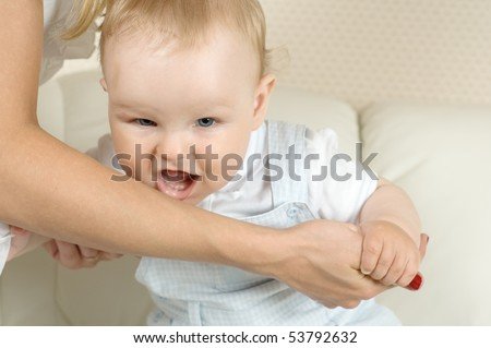The baby wishes to bite mum for a hand - stock photo