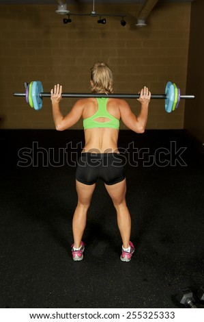 The back a young brunette doing a squat with a barbell in a gym. - stock photo