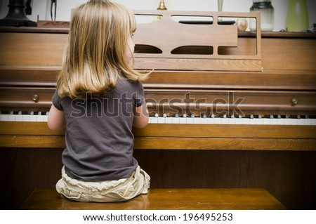 The back of a blond girl, sitting playing a brown, wooden piano. - stock photo