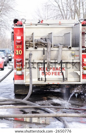 The back of a Fire Truck hooked up to the hydrants - stock photo