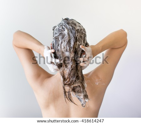 The back of a woman washing her hair full of suds in front of a white background.  - stock photo