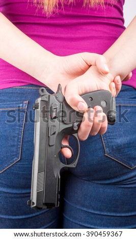 The back of a woman with a pistol in her hand - stock photo
