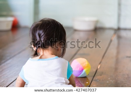 The back of baby girl looking at her ball - stock photo