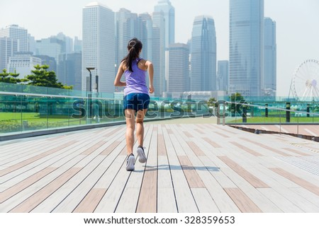 The back view of the jogging girl - stock photo