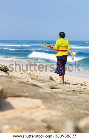 The balinese woman goes along the sand beach and carries a silver tray with offerings to spirits - stock photo