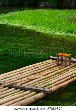 The bamboo raft floating in the clear water - stock photo
