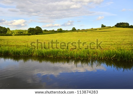 The banks of a river, with bushes and trees. - stock photo