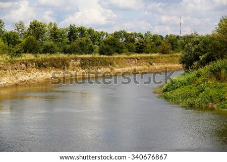 The banks of a river with trees - stock photo