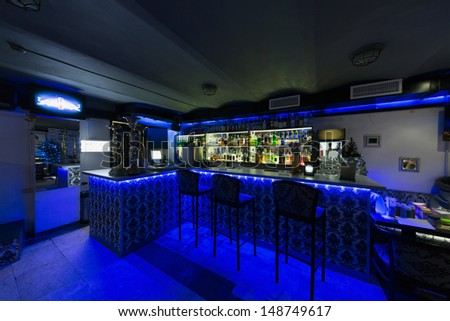 The bar counter in cafe with three chairs illuminated with blue light - stock photo