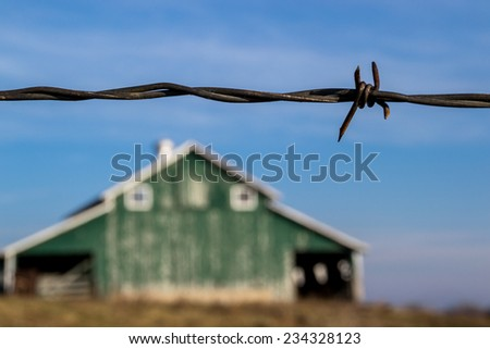 The barbed wire fence with old rural barn in the background. - stock photo