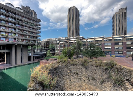 The Barbican Center, London is one of the most popular and famous examples of Brutalist architecture in the world. In the foreground of the photo can be seen the ancient remains of the wall of London - stock photo