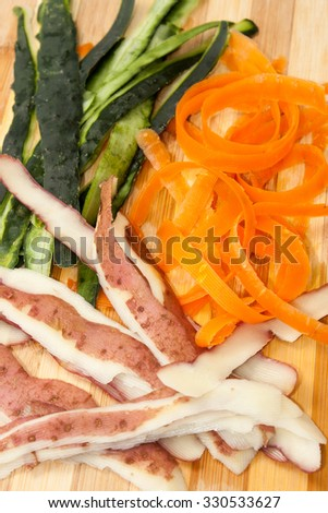 The bark from cucumber, carrots and potatoes on wooden board. - stock photo
