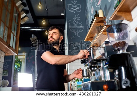 The bartender makes the coffee, cappuccino, cocoa, drink at the bar. Bartender job. - stock photo