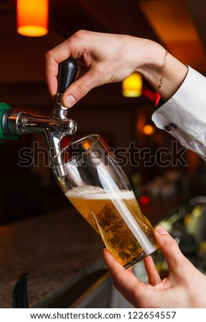the bartender pours the beer into a glass from the tap - stock photo
