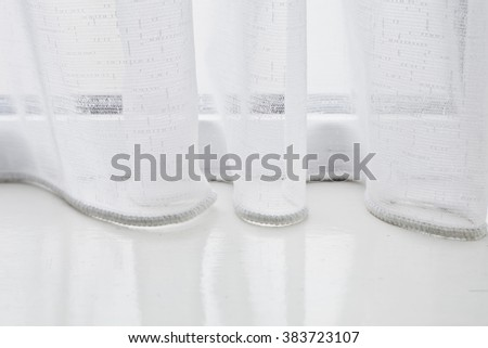The base of a net curtain on a white windowsill - stock photo