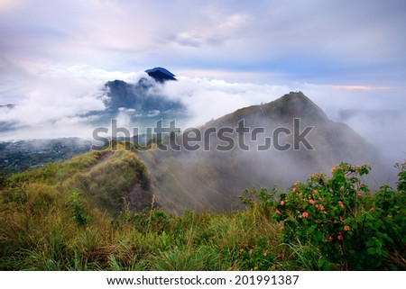 The Batur volcano crater in cloudy weather with Agung volcano in behind, Bali, Indonesia - stock photo