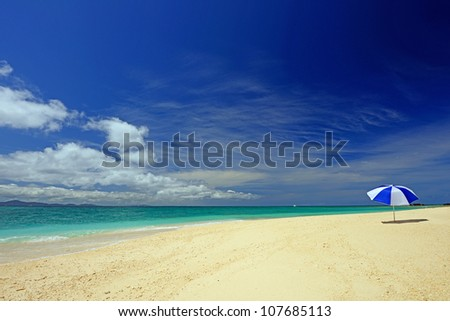 The beach and the beach umbrella of midsummer. - stock photo