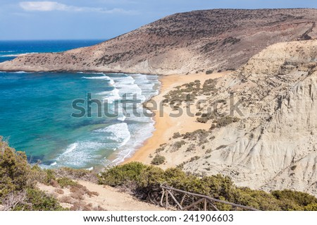 The beach Potamos at the northwest coast of Gavdos.It is a long beach with reddish sand and shallow water formed at the exit of a small canyon with majestic geological clay formations and steep cliffs - stock photo