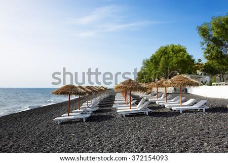 The beach with black volcanic stones at Santorini island, Greece - stock photo