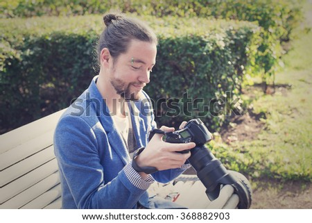 The bearded hipster photographer in blue jacket looks pictures he made at a photo shoot at the park. - stock photo
