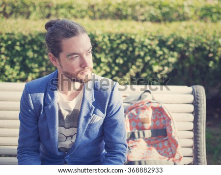 The bearded hipster photographer in blue jacket waits for a meeting with someone in a park in St. Petersburg. - stock photo
