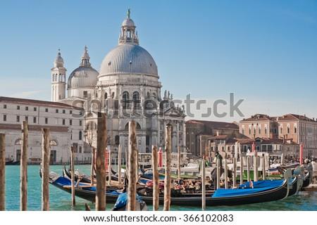 The beautiful and famous tourist destination the Basilica Santa Maria della Salute church with venetian gondolas in sunny weather on the Grand Canal, Venice, Italy - stock photo