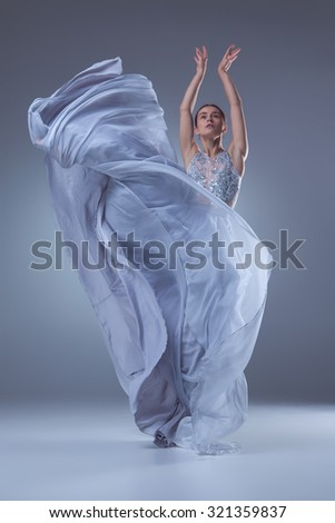 The beautiful ballerina dancing in long lilac dress on lilac background - stock photo