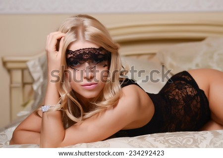 The beautiful blonde girl on a bed - stock photo