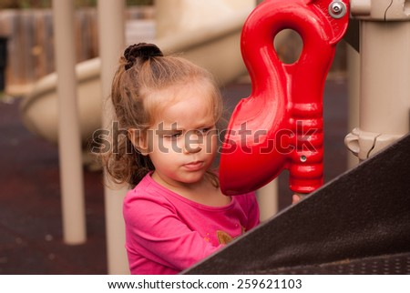 The beautiful blonde  girl play on the playground - stock photo