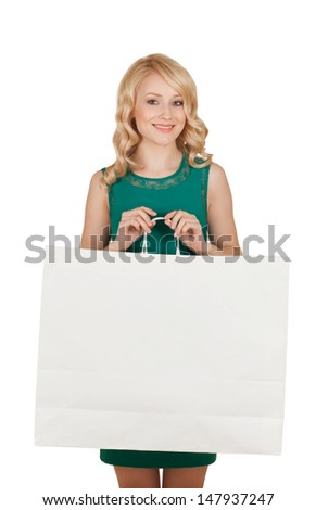 the beautiful blonde in a green dress holds a big package with purchases - stock photo