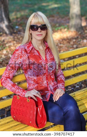 The beautiful blonde in the park in early autumn - stock photo