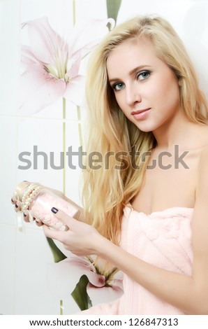 The beautiful blonde woman in a bathroom - stock photo