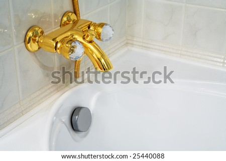 The beautiful bronze faucet and white bath - stock photo