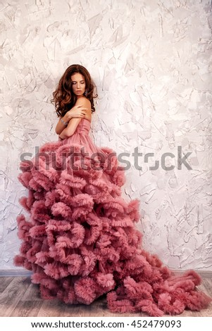 The beautiful brunette woman with curly hair, tender makeup posing in a wedding dress. - stock photo