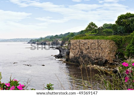 The beautiful coast of Rhode Island with wild flowers in the foreground. - stock photo