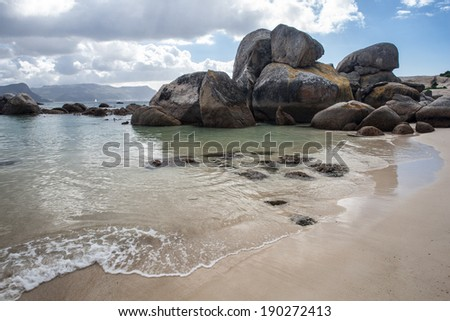 The beautiful coastline of False Bay, South Africa, is strewn with massive boulders, tide pools, and white sand beaches. This area is near Table Mountain National Park. - stock photo