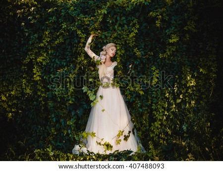 The beautiful countess in a long pastel  dress  is walking in a green forest full of branches, elf,  Princess in vintage dress, the queen of the forest,fashionable toning creative computer colors - stock photo