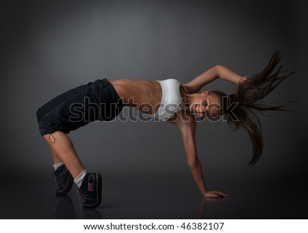 The beautiful dancing girl on a grey background. Modern dances. - stock photo