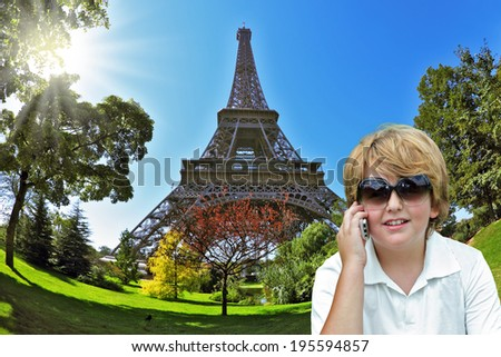 The beautiful fair-haired boy cheerfully stirs with friends by the mobile phone. Background - the Eiffel Tower. The picture is made a lens the Fisheye - stock photo