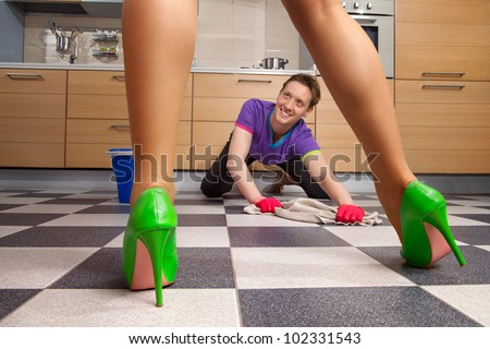 The beautiful female legs standing  against of young man cleaning floor - stock photo