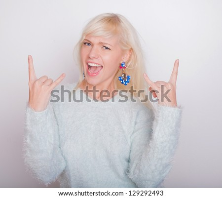 the beautiful fresh blonde the girl in a jacket and on a white background is surprised and very glad - stock photo