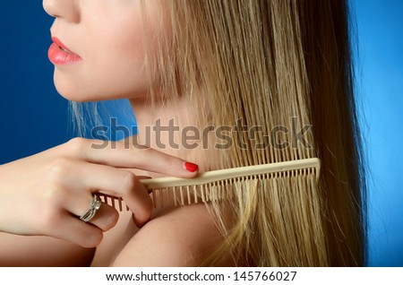 The beautiful girl brushes hair on blue - stock photo