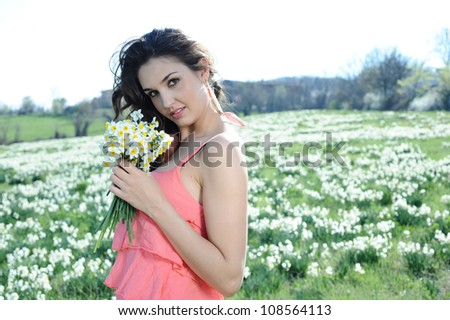the beautiful girl collects flowers in the meadow - stock photo