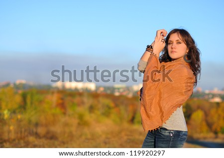 The beautiful girl in a cape against the city - stock photo