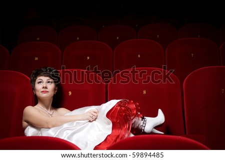 The beautiful girl in a white dress sits in a red armchair at a cinema alone - stock photo