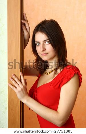 The beautiful girl waits at a door - stock photo