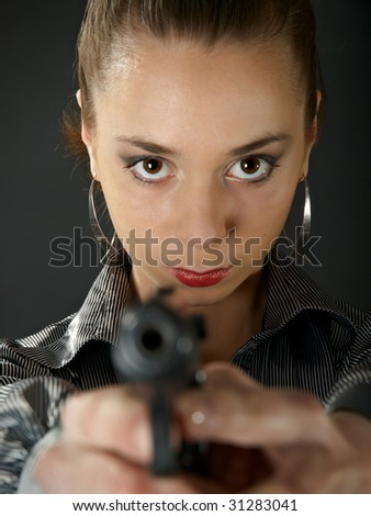The beautiful girl with a gun against a dark background - stock photo